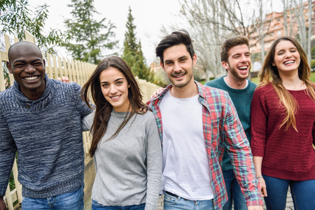 young friends: Group of multi-ethnic young people laughing together outdoors in urban background. group of people walking together wearing casual clothes