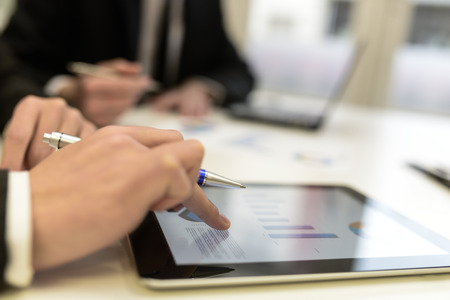finger: Close-up of a modern business team using tablet computer to work with financial data