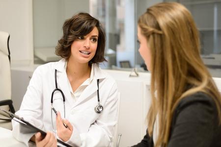 그녀의 여성 환자에게 진단을 설명 여성 의사 스톡 콘텐츠