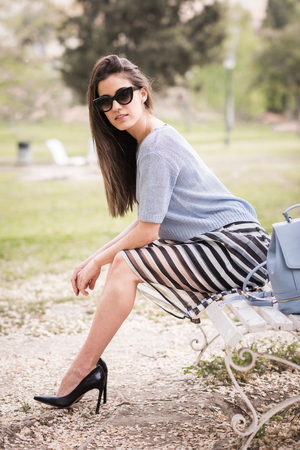 Mujer joven con las piernas hermosas en el fondo urbano con ropa casual. Chica con gafas de sol de la falda de rayas y un suéter que se sienta en un banco de un parque urbano