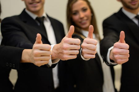 Close-up of business team holding their thumbs up Фото со стока