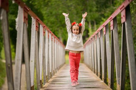 Cute little girl with four years old having fun in a rural bridge