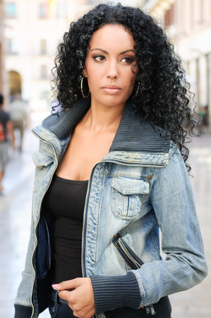 black hair: Portrait of a young black woman, afro hairstyle, wearing dening jacket in urban background