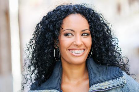 중괄호로 웃고있는 젊은 흑인 여성의 초상화 스톡 콘텐츠
