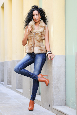 urban fashion: Portrait of a young black woman, afro hairstyle, wearing blue jeans and fur vest in urban background Stock Photo