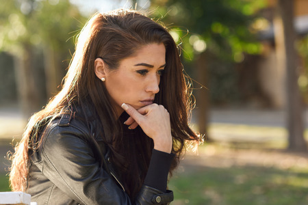 woman serious: Thoughtful woman sitting alone outdoors. Girl worried in an urban park Stock Photo