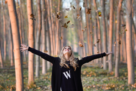 Portrait of a happy woman playing with autumn leaves in forest Stock Photo