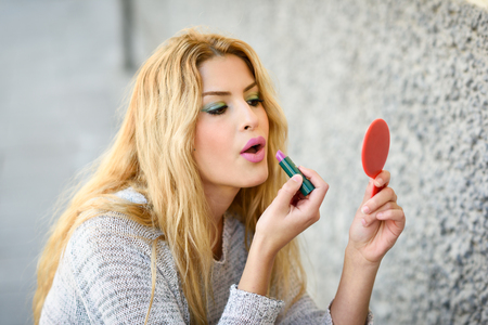 applying: Young blonde woman applying lipstick looking at mirror in the street. Girl making-up herself in urban background using pink lipstick.