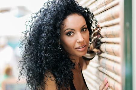 Close-up d'une jeune femme noire, coiffure afro, avec des cheveux très bouclés sourire en arrière-plan urbain