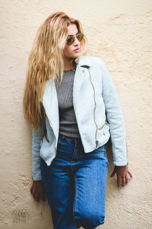 Portrait of beautiful young blonde woman with curly hair. Girl wearing leather jacket, blue jeans and aviator sunglasses in urban background.