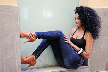 Portrait of a young black woman, afro hairstyle, wearing blue jeans in urban background Stock Photo