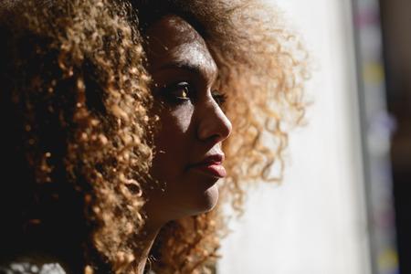 ojos verdes: Retrato de primer plano OFL mujer afroamericana joven con peinado afro y los ojos verdes