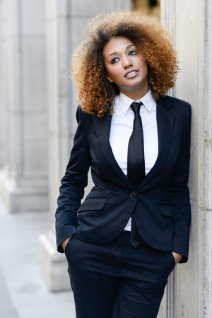 black lady: Portrait of beautiful black businesswoman wearing suit and tie in urban background
