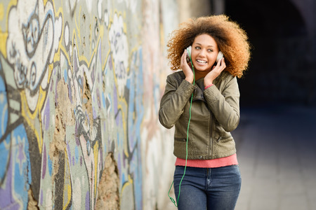 urban style: Portrait of young attractive black girl in urban background listening to the music with headphones. Woman wearing leather jacket and blue jeans with afro hairstyle