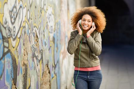 listening to music: Retrato de joven negro atractivo en fondo urbano que escucha la m�sica con los auriculares. Mujer que desgasta la chaqueta de cuero y pantalones vaqueros azules con el peinado afro Foto de archivo
