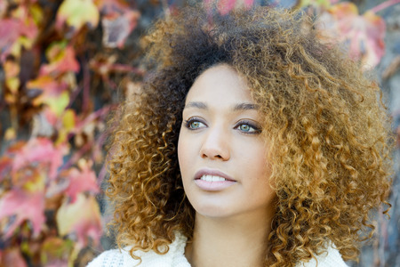 hairstyle: Beautiful young African American woman with afro hairstyle and green eyes wearing white winter dress with autumn leaves in the background.