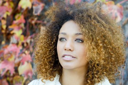 modelos negras: mujer africana joven hermosa con el peinado afro americana y ojos verdes con un vestido blanco de invierno con las hojas de otoño en el fondo.