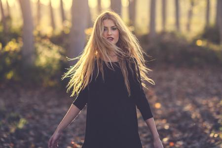 Giovane donna bionda che balla in foresta di pioppo. Donna che indossa abito nero con i capelli volanti