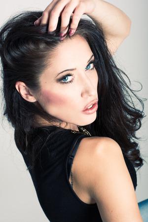 ojos marrones: mujer morena con ojos azules usar suéter y pantalones vaqueros azules sobre fondo blanco. lanzamiento del estudio