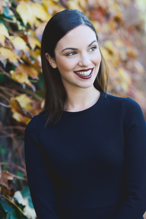 urban fashion: Beautiful young woman, model of fashion, wearing black dress smiling in urban background with autumn colors. Very straight hair styling