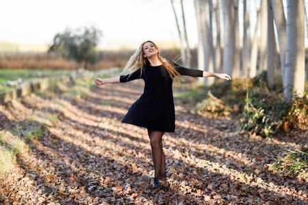 donna che balla: Dancing della giovane donna bionda nella foresta di pioppo. La donna che indossa un abito nero con i capelli di volo