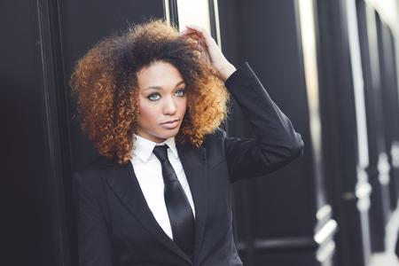 femme africaine: Portrait de la belle femme d'affaires noir portant costume et cravate en arrière-plan urbain. Modèle de la mode avec coiffure afro.