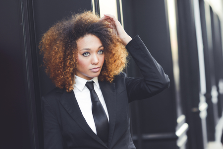 young woman face: Portrait of beautiful black businesswoman wearing suit and tie in urban background. Model of fashion with afro hairstyle. Stock Photo