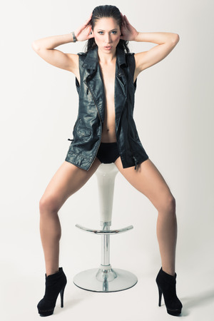 schöne augen: Brunette woman with blue eyes wearing black leather jacket and panties on white background. Studio shoot