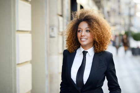 donne eleganti: Ritratto di bella imprenditrice che indossa abito nero e cravatta sorridente in fondo urbano. Donna con acconciatura afro. Archivio Fotografico