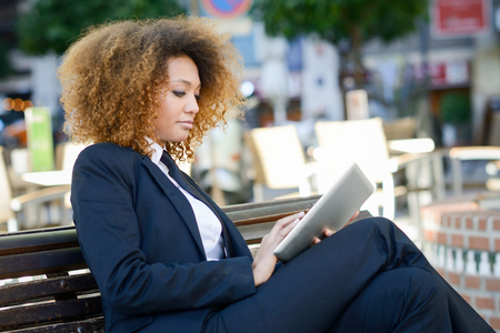 green and black: Beautiful black woman using tablet computer in urban background. Businesswoman wearing suit with trousers and tie, afro hairstyle.