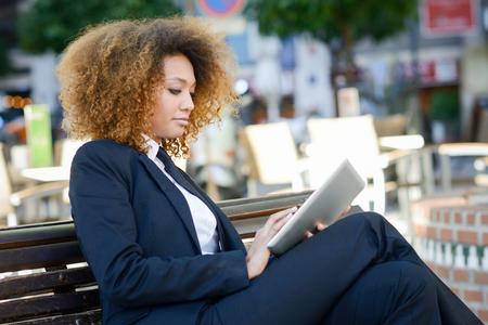 ojos negros: Hermosa mujer de negro con tablet PC en el fondo urbano. Empresaria con traje con pantalón y corbata, peinado afro.