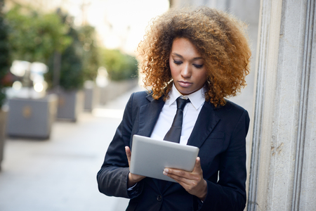 african business: Beautiful black curly hair african woman using tablet computer in town. Businesswoman wearing suit with trousers and tie