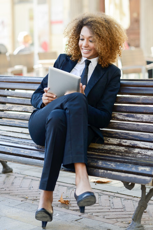 businesswoman suit: Beautiful black woman smiling and using tablet computer in urban background Businesswoman wearing suit with trousers and tie. Stock Photo
