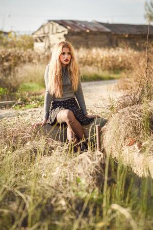 hair blond: Bella giovane donna bionda, modello di modo, in fondo rurale. Ragazza che indossa maglione e gonna.