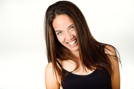 ojos verdes: mujer joven y bella sin maquillaje reír. Hermosa chica con ojos verdes, modelo de la manera que desgasta la tapa del tanque negro sobre fondo blanco. Foto de archivo