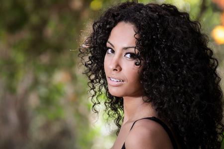 attraktiv: Portrait einer jungen schwarzen Frau, Afro-Frisur, im städtischen Hintergrund