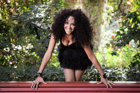 hair curly: Retrato de una mujer joven negro sonriente con los frenos en parque urbano.