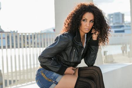 Portrait d'une jeune femme noire, coiffure afro, en arrière-plan urbain. Fille en short denim jear et veste en cuir.