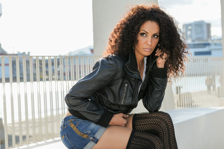 citylife: Portrait of a young black woman, afro hairstyle, in urban background. Girl wearing denim jear shorts and leather jacket.