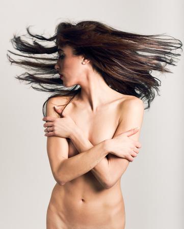 mujer sexy desnuda: Mujer desnuda hermosa con el pelo móvil en el fondo blanco.