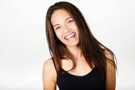 Beautiful young woman without make-up laughing. Beautiful girl with green eyes, model of fashion wearing black tank top on white background.