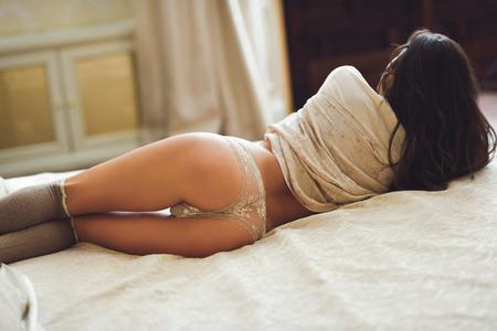 junge nackte mädchen: Zurück von sexy junge Frau in Dessous auf dem Bett posieren. Gleichaltrige Mädchen mit weißen Höschen, T-Shirt und große Socken in ihrem Schlafzimmer Lizenzfreie Bilder