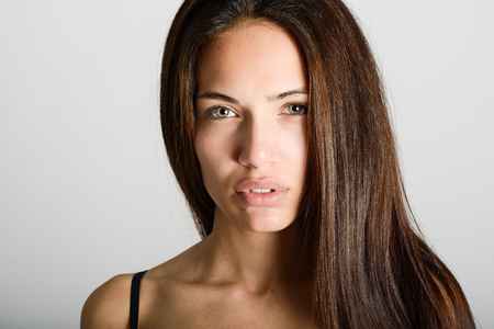 Beautiful young woman without make-up. Beautiful girl with green eyes, model of fashion wearing black tank top on white background.