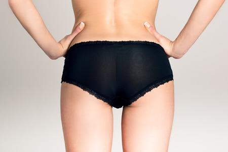 thong woman: Female ass wearing black panties, white background
