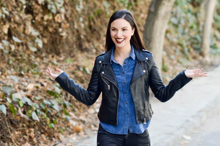 Beautiful young woman, smiling in urban background. Girl wearing leather jacket and blue shirt Stock Photo