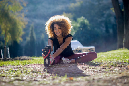 black lady: young fitness black woman runner stretching legs after run