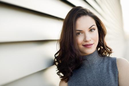 Hermosa mujer joven, modelo de la moda, sonriente en el fondo urbano Foto de archivo