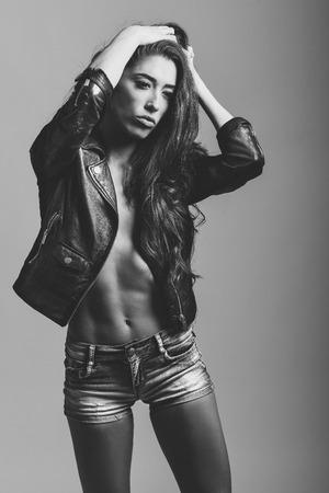in jeans: Cuerpo de la mujer hermosa en dril de algodón pantalones jeans y chaqueta de cuero negro. foto de estudio en blanco y negro. Foto de archivo