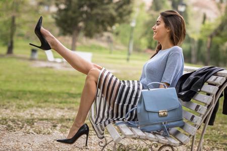 カジュアルな服を身に着けている都市公園で美脚を持つ若い女性の肖像画。ストライプ スカート、セーターとハイヒールを身に着けている女の子
