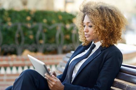 도시 벤치에 태블릿 컴퓨터를 사용하는 아름 다운 검은 곱슬 머리 흑인 여자. 사업가 바지와 넥타이, 아프리카 헤어 스타일 양복을 입고.